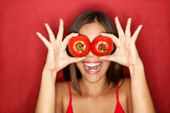 Junge Frau hält sich Tomaten vor die Augen.