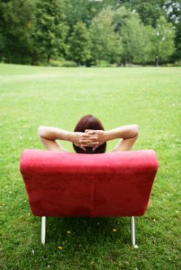 Junge Frau liegt auf einer Couch in mitten der Natur