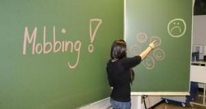 """Lehrerin an einer Tafel mit dem Schriftzug """"Mobbing"""""""