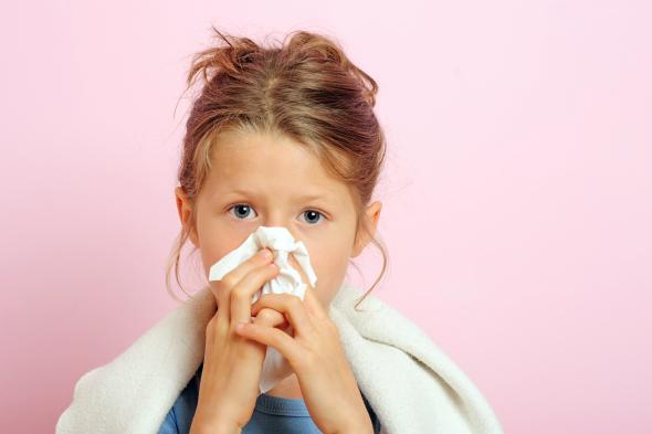 Mädchen hat Heuschnupfen und putzt sich die Nase.