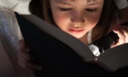 Lesen in der Dämmerung - Mädchen liest mit Taschenlampe ein Buch im Bett