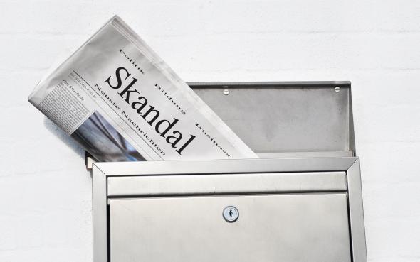 Zeitung mit Schlagzeile im Briefkasten