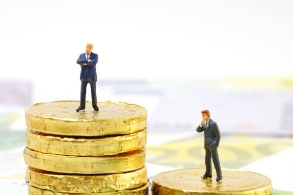 Zwei Figuren auf unterschiedlich hohen Geldstapeln.