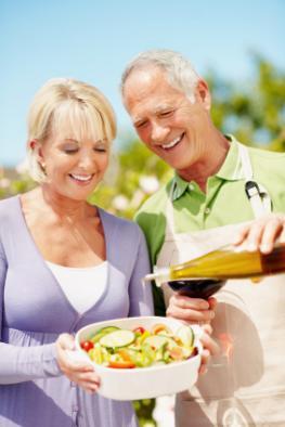Älteres Ehepaar ernährt sich mediterran: Der Mann gießt Olivenöl auf den Salat.