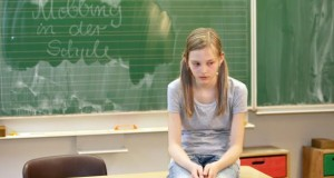 """Schülerin sitzt auf einem Tisch - im Hintergrund steht an der Tafel """"Mobbing in der Schule"""""""