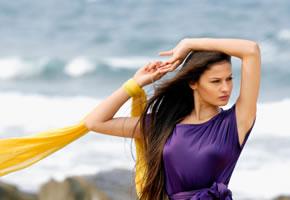 Ein Model am Strand in einem Lila Kleid