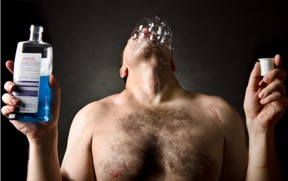 Ein Mann spült seinen Mund mit Mundwasser.