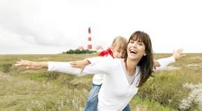 Friesland Varel: Mutter mit Kind, im Hintergrund ist ein Leuchtturm