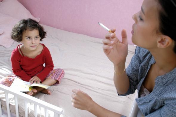Eine Mutter raucht in Gegenwart der kleinen Tochter.