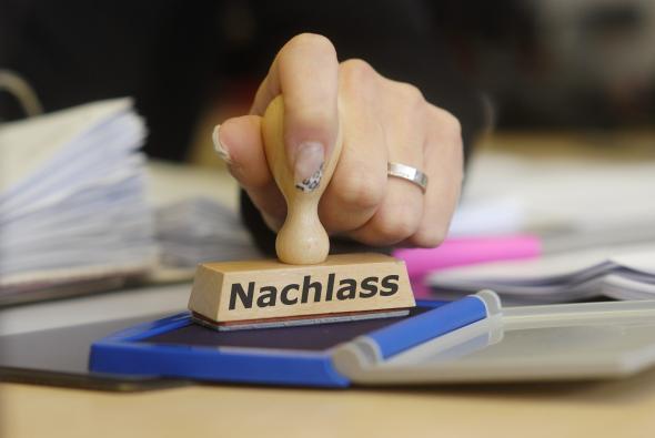 """Verwaltungsangestellte benutzt einen Stempel mit der Aufschrift """"Nachlass"""""""