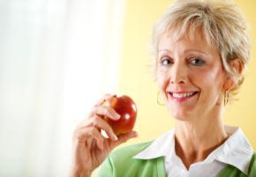 Eine Frau zeigt ihren Apfel