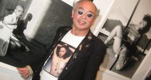 Nobuyoshi Araki posiert vor seinen erotischen Bildern.
