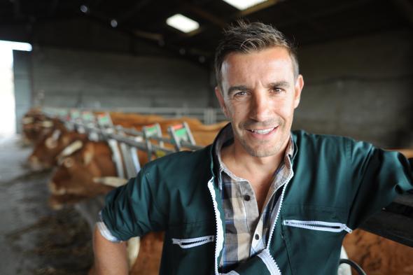 Ein Bauer steht im Stall bei den Kühen.