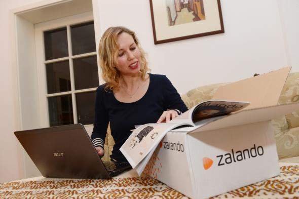 Junge Frau kauft im Internet bei Zalando ein.