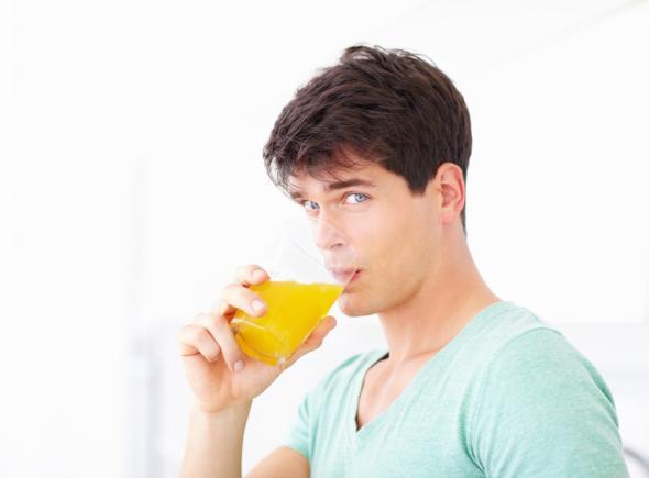 Junger Mann trinkt einen Orangensaft. mit Vitamin C.