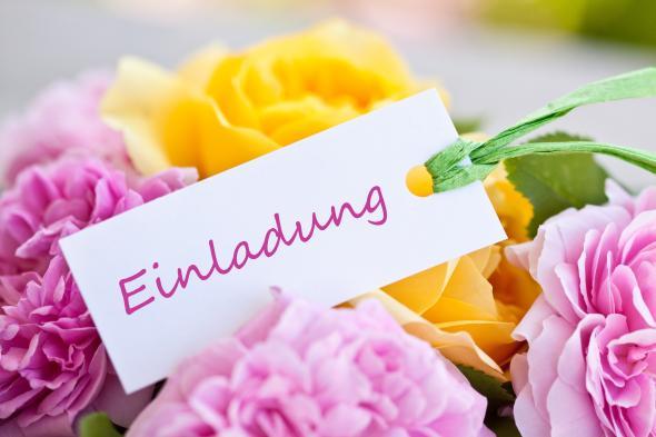 Blumenstrauß mit einer Einladungskarte.