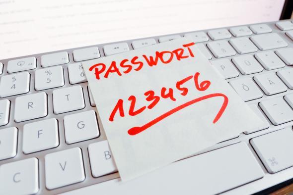 """Ein Zettel liegt auf einer Notebook-Tastatur - auf dem steht: """"Passwort 123456"""""""