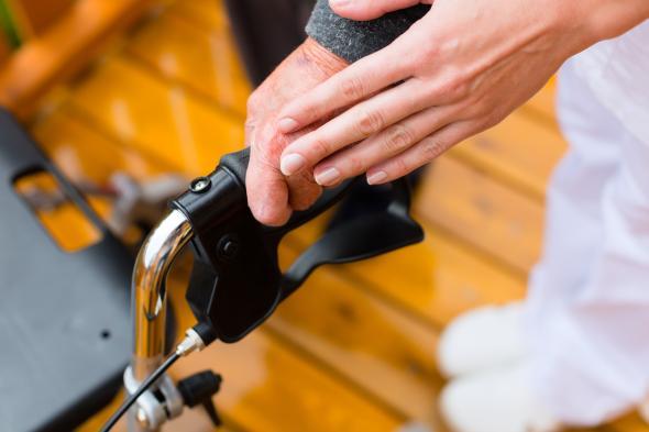 Ältere Person mit einem Gehwagen wird von einer Pflegekraft gestützt.