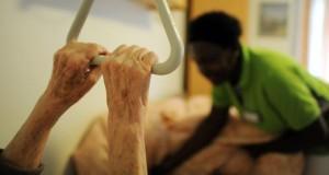 Pflegehausbewohnerin hält sich an einem Bettgriff fest.