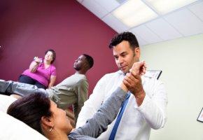 Physiotherapeut arbeitet mit einer Schmerzpatientin