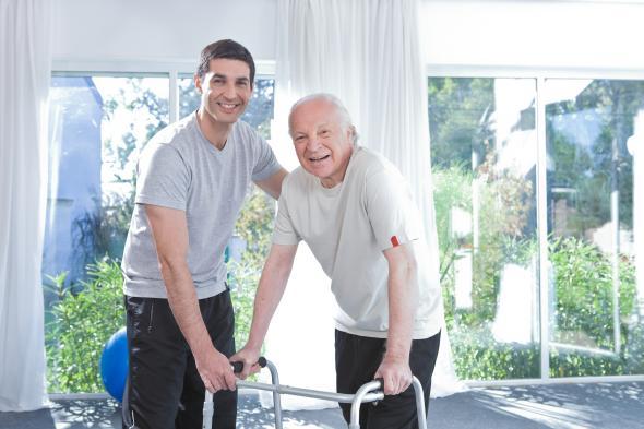 Älterer Mann und sein Physiotherapeut macht Gehversuche mit einem Gehgestell.