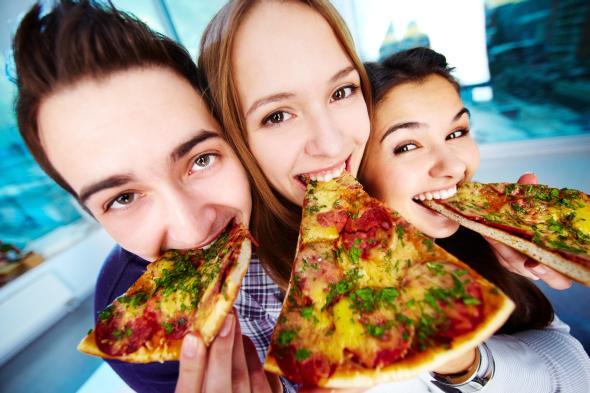 Teenager essen ein großes Stück Pizza.