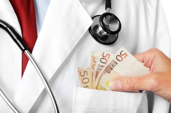 Jemand steckt einem Mediziner ein paar 50 Euro-Scheine in die Tasche.