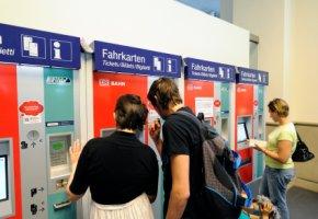 Reisende vor einem Fahrkartenautomaten
