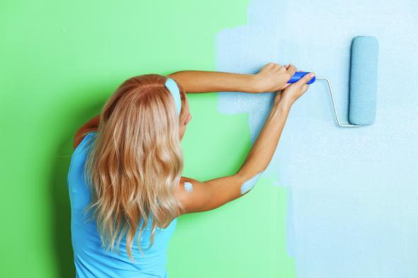 Neue Farbe mit dem Farbroller auf die Wand auftragen.