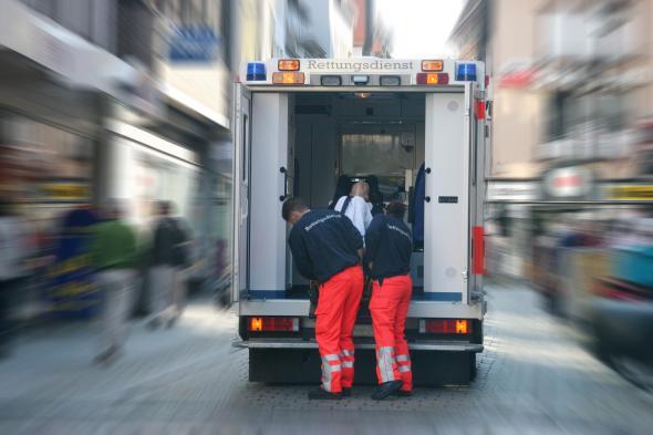 Rettungssanitäter laden eine kranke Person in ihren Rettungswagen.