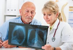 Ärztin erklärt dem älteren Patienten das Röntgenbild