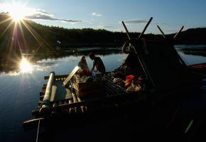 Romantik: Pärchen auf seinem Floß beim Sonnenuntergang