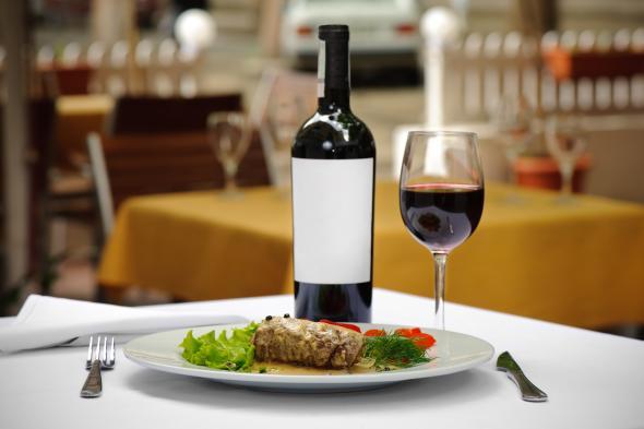 Ein Teller mit einem Steak und ein Glas Rotwein.