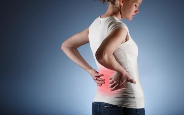 Junge Frau hat Rückenschmerzen.