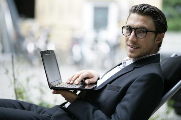 Ein Mann sitzt draußen mit seinem Laptop.
