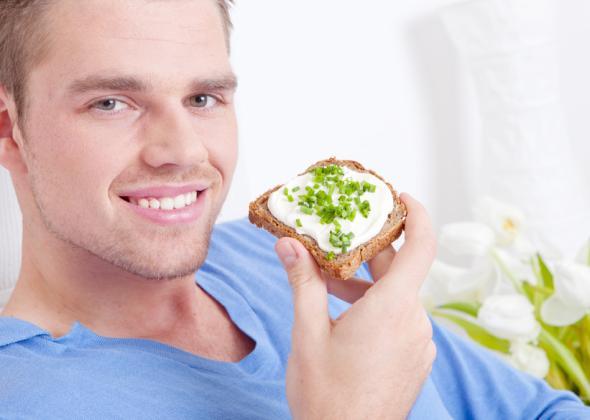 Vegetarisch Essen - Ein Mann isst ein Vollkornbrot mit Frischkäse und Schnittlauch.