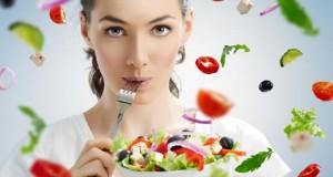 Junge Frau isst einen Salat.