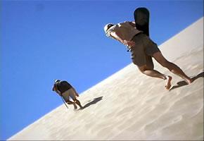 Junge Leute laufen mit ihren Boards die Dünen hoch.
