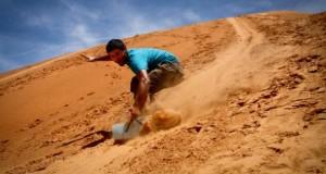 Junger Mann gleitet mit einem Board die Sanddünen hinunter.