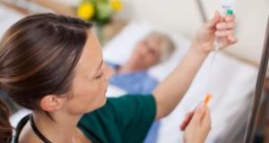 Krankenschwester stellt eine Infusion ein.