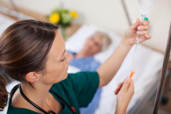 Schmerzbehandlung - Krankenschwester stellt eine Infusion ein.