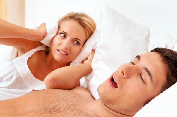 Ein Mann schnarcht, seine Frau ist nicht begeistert.