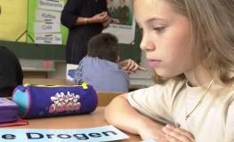 """Mädchen sitzt vor Schildern mit dem Schriftzug """"Drogen""""."""