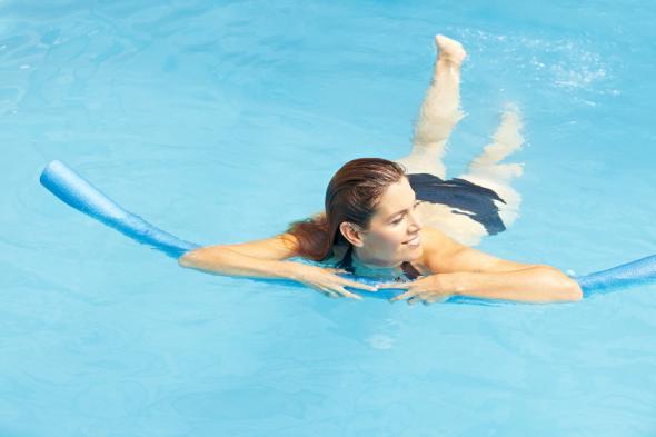 Eine lernt im Schwimmbad schwimmen.