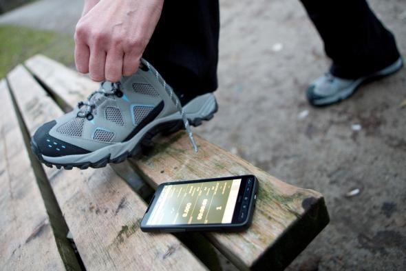 Jogger bindet sich die Laufschuhe, auf einer Parkbank liegt ein Smartphone zum messen der Laufdaten.