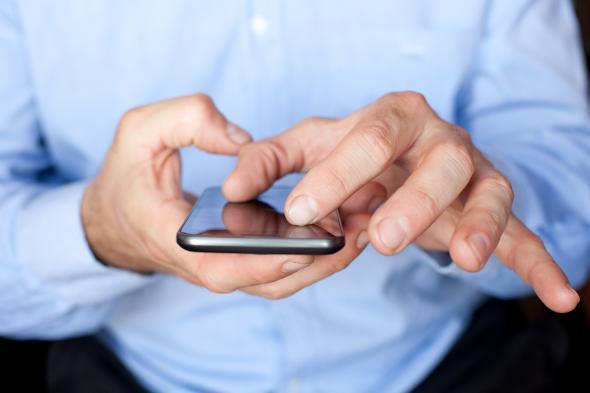 Ein Mann tippt und zoomt auf seinem Smartphone.