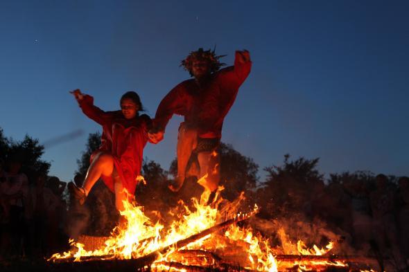 Mittsommer - Pärchen springt an der Sommersonnenwende über das Feuer.