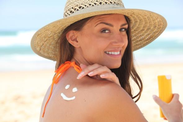 Eine Frau cremt sich mit einer Sonnenschutzcreme ein.