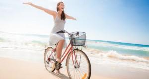 Junge Frau fährt freihändisch und glücklich auf dem Fahrrad am Strand entlang.