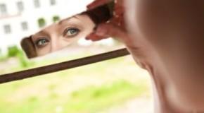 Spiegelbild - Eine junge Frau schaut in einen Spiegel